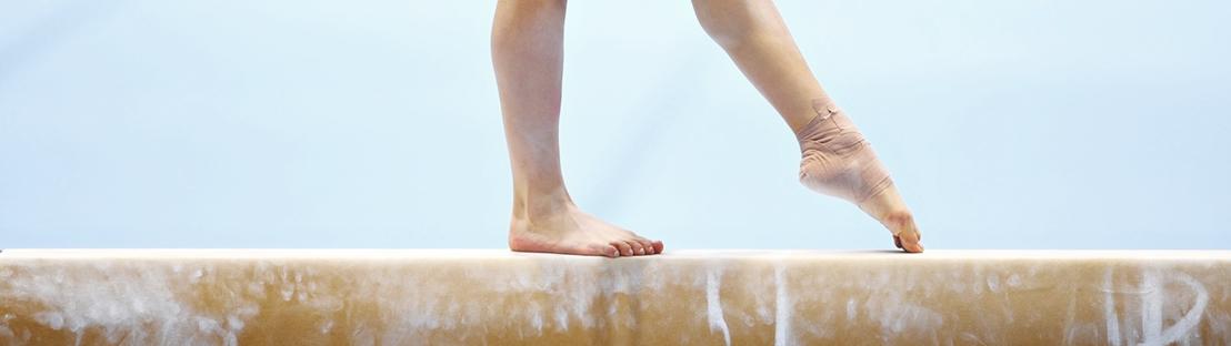 girl tumbling on beam